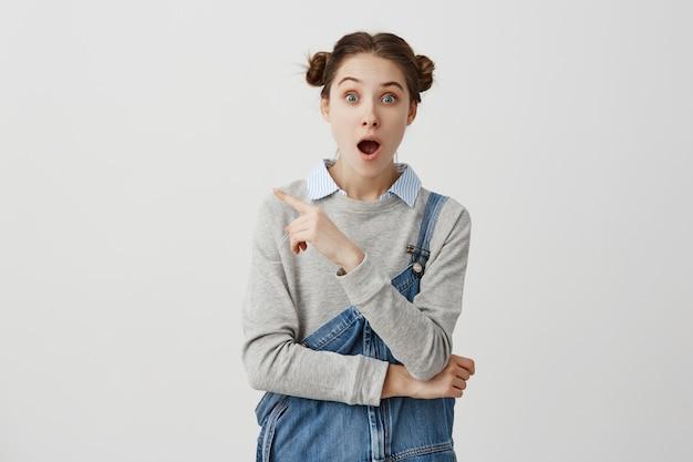 Garota surpresa com penteado engraçado, apontando o dedo sobre uma parede branca com a boca aberta e os olhos esbugalhados. conceito de inesperado mostrando pelo ilustrador feminino. copie o espaço