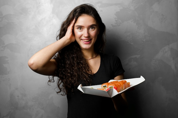 Garota surpresa com sushi conjunto filadélfia rola em uma caixa de papel garota feliz segurando sobre um fundo cinza. entrega de alimentos.