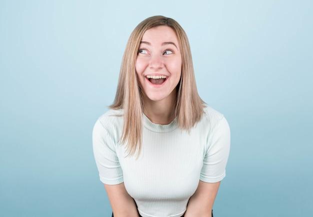 Garota surpresa com um top azul sobre um fundo azul