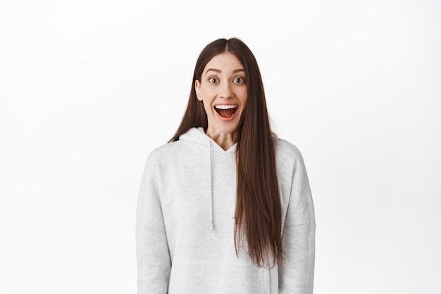 Garota surpresa e emocionada, sorrindo, maravilhada com a boca aberta e olhando para a frente fascinada, respirando e emocionando o evento, posando contra uma parede branca