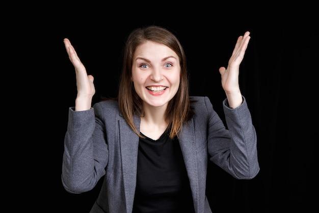 Garota surpresa e muito emocionada em uma jaqueta cinza sobre um fundo preto
