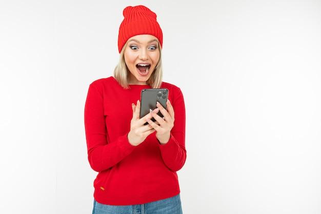 Garota surpresa em roupas vermelhas com um smartphone nas mãos dela sobre um fundo com espaço de cópia