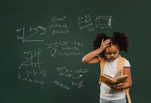 Garota surpresa em tiro médio lendo livro Foto gratuita