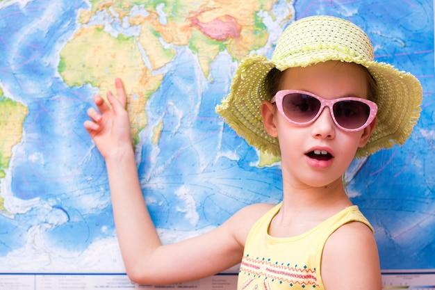 Garota surpresa em um chapéu e óculos de sol mostra em um mapa do mundo