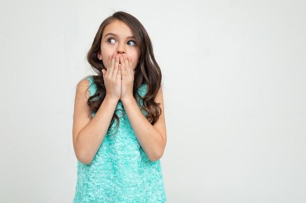 Garota surpresa em um vestido azul cobriu a boca com as mãos em uma parede branca do estúdio