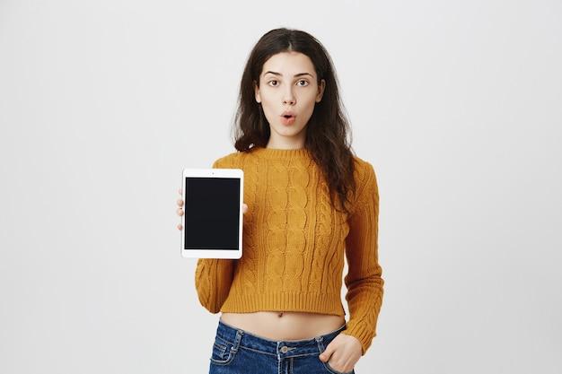 Garota surpresa mostrando promoção de aplicativo, tela de tablet digital