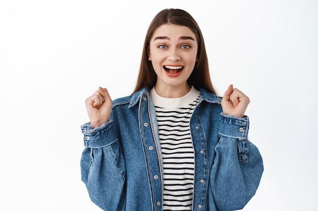 Garota surpresa se regozijando com as boas notícias, batendo os punhos como campeã ou vencedora, comemorando a vitória, atingindo a meta, triunfando sobre a vitória ou conquista, de pé sobre a parede branca