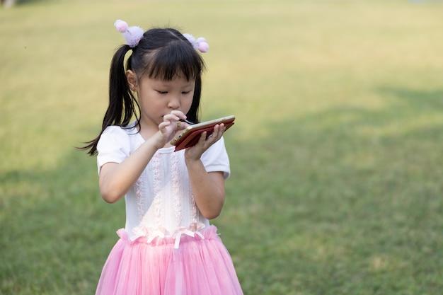 Garota tailandesa de crianças em pé está assistindo filmes de desenho animado no smartphone com sistema de alta velocidade 4g wi-fi no jardim da gronelândia
