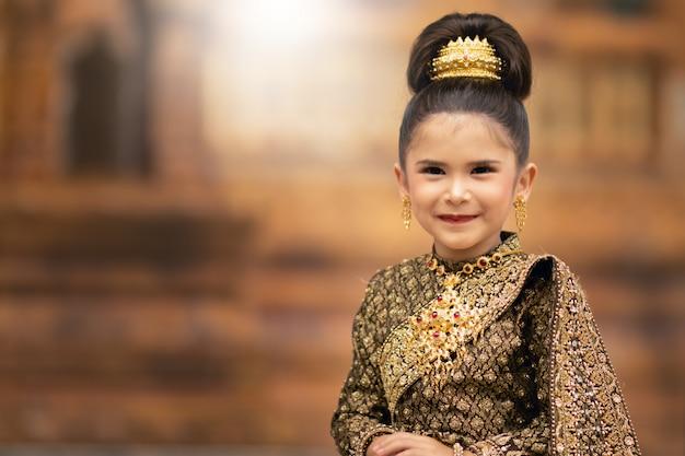 Garota tailandesa em traje tailandês posando com feliz.
