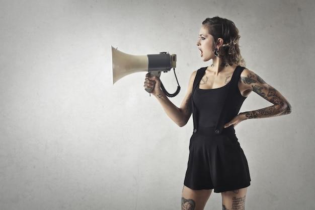 Garota tatuada gritando em um megafone