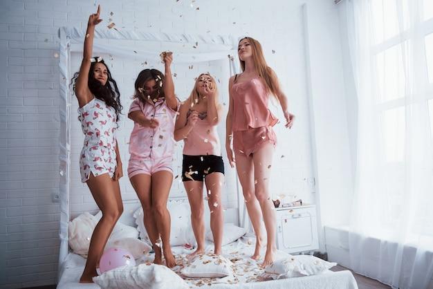 Garota tem boas formas do corpo. confetes no ar. as meninas se divertem na cama branca no quarto agradável