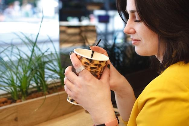 Garota tem um copo de papel com estampa de leopardo e café com leite no café.