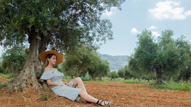 Garota tem um descanso no jardim de oliveira grega