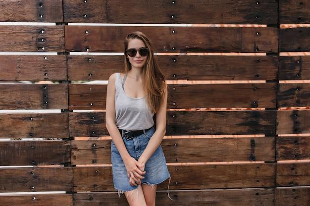 Garota tímida com saia jeans da moda, posando perto da parede de madeira. retrato ao ar livre da adorável senhora caucasiana com penteado reto.