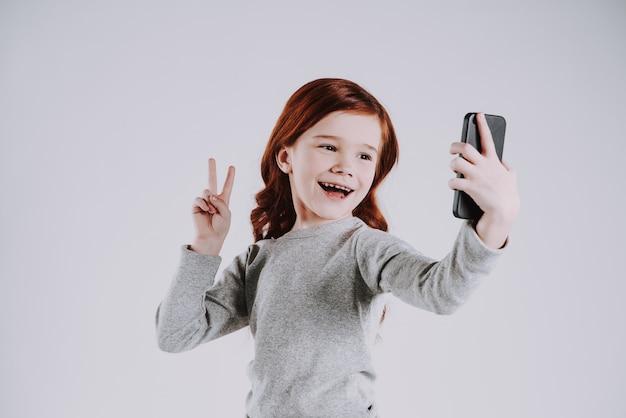 Garota tira fotos de si mesma no telefone, mostrar sinal de vitória.