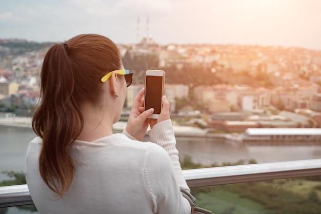 Garota tira fotos no panorama de telefone da cidade.