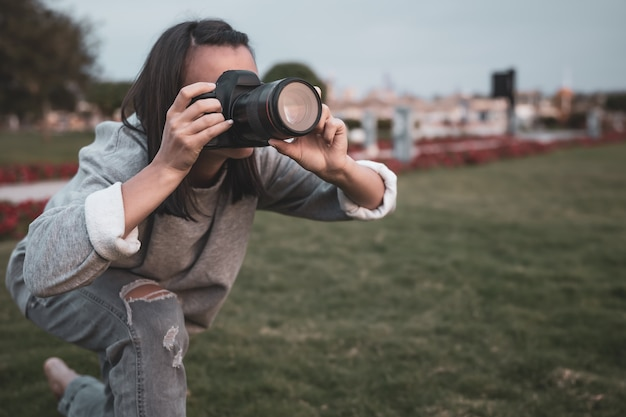 Garota tira uma foto com uma câmera slr profissional no verão ao ar livre.