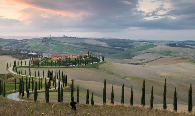 Garota tira uma foto de uma fazenda e uma estrada com ciprestes ao pôr do sol em val dorcia, itália