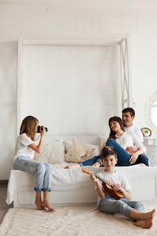Garota tirando foto de seus pais e seu irmão tocando cavaquinho em casa