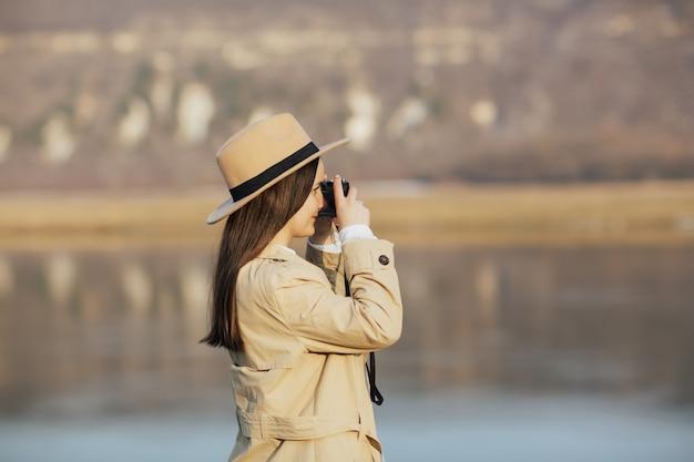 Garota tirando fotos ao ar livre na montanha com uma câmera fotográfica