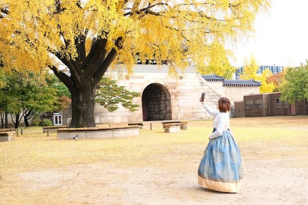 Garota tirando uma foto com vestido hanbok no palácio gyeongbokgung