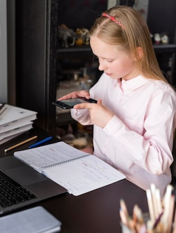 Garota tirando uma foto de suas anotações com o telefone