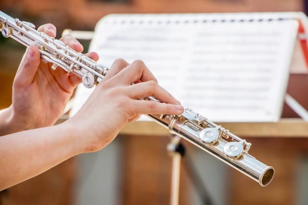 Garota toca flauta. flauta nas mãos do músico durante a execução da peça musical
