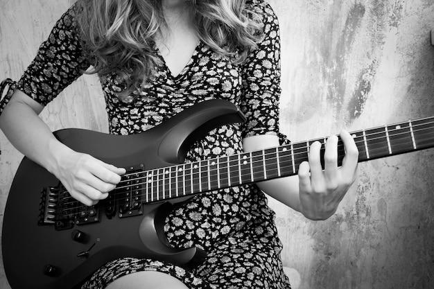 Garota toca guitarra elétrica.