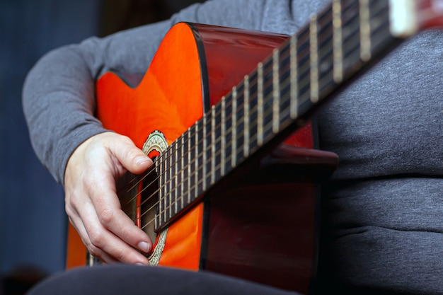 Garota toca um violão laranja com cordas de nylon.