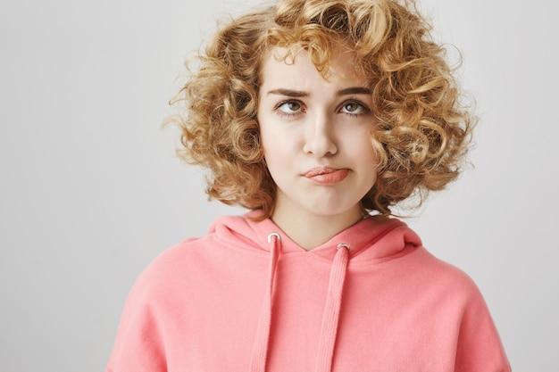 Garota tola entediada soprando um cacho do cabelo, apertando os olhos