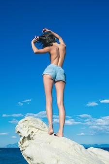 Garota tomando banho de sol em topless na pedra. férias de verão e viagens para o oceano. maldivas ou praia de miami. mulher sexy no mar do caribe, nas bahamas.