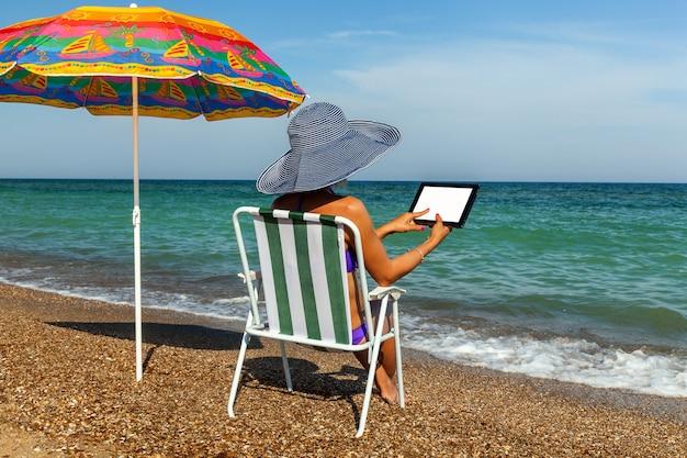 Garota tomando banho de sol na praia com uma mulher laptop sob uma cadeira de guarda-chuva