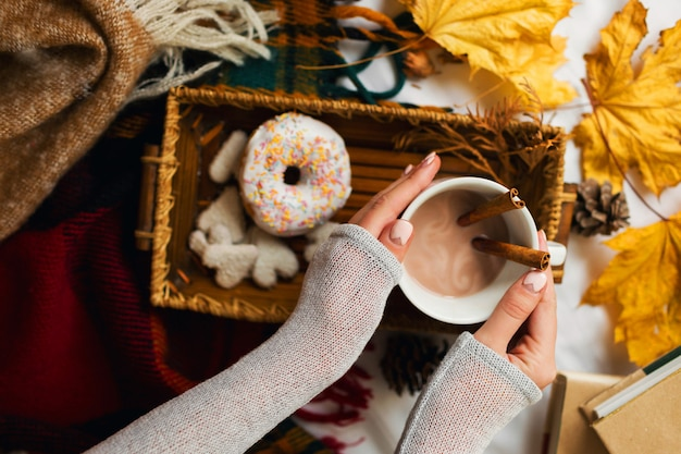 Garota tomando café da manhã saboroso na cama, na bandeja de madeira com uma xícara de cacau, canela, biscoitos e donuts glaceados.