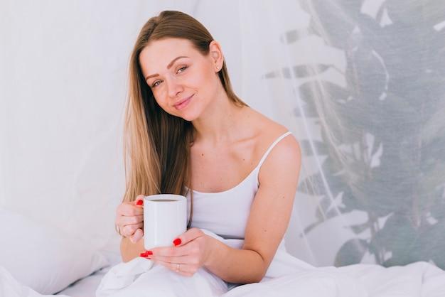Garota tomando café na cama