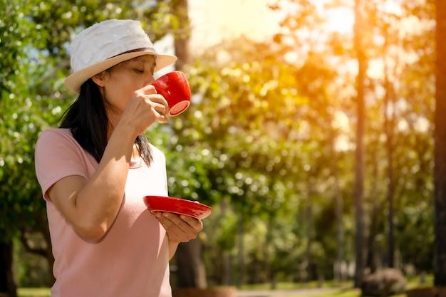 Garota tomando café no exterior da natureza bonita nas colinas, conjunto de xícara de café vermelho