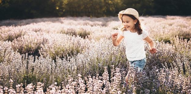 Garota torcendo e correndo por um campo de lavanda durante um dia ensolarado de verão