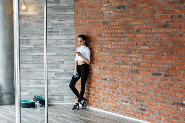 Garota trabalha com seu smartphone depois ou antes de um treino no ginásio