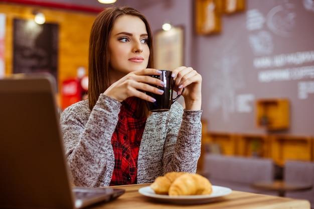 Garota trabalha em um laptop e bebe chá.
