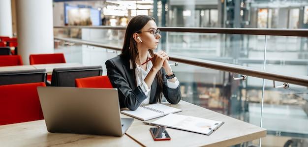 Garota trabalha em um laptop no local de trabalho. mulher de negócios de sucesso cria uma startup e toma decisões.