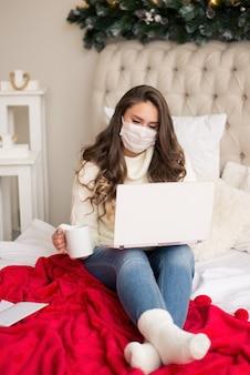 Garota trabalha online, de casa, deita na cama, vídeo link