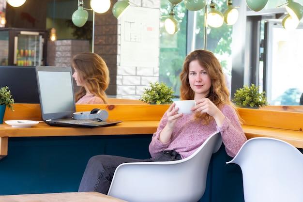Garota trabalha para um laptop. trabalho remoto, online. garota em um café com uma xícara de café.