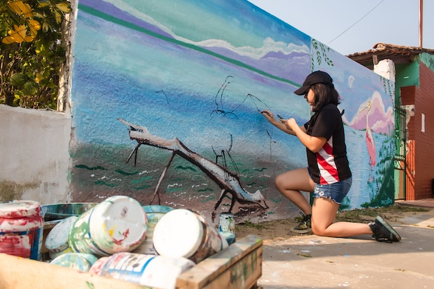 Garota trabalhadora pintando uma parede de rua com pincéis.