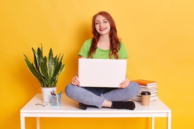 Garota trabalhando duro em algum projeto, fazendo uma pausa, sentada na mesa branca e segurando o laptop