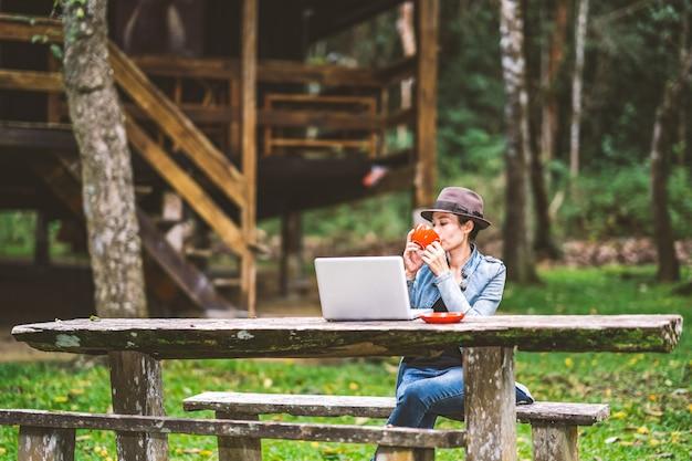 Garota trabalhando e tomando café na mesa no tempo de férias de férias na natureza de colinas