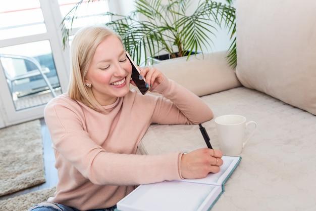 Garota trabalhando em casa, falando ao telefone e escrevendo notas em seu caderno.