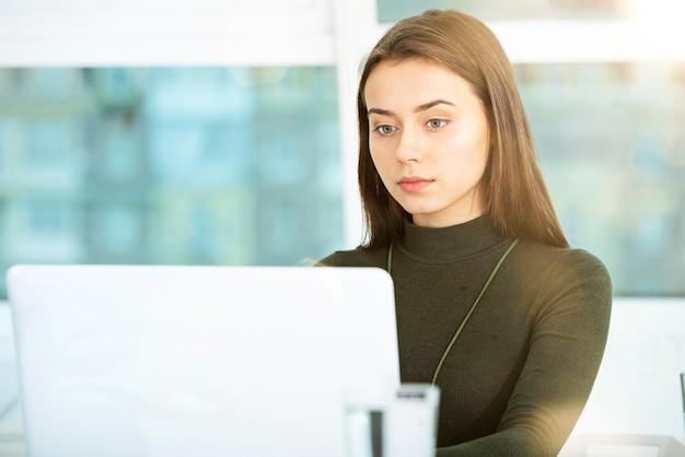 Garota trabalhando em um laptop em um escritório moderno