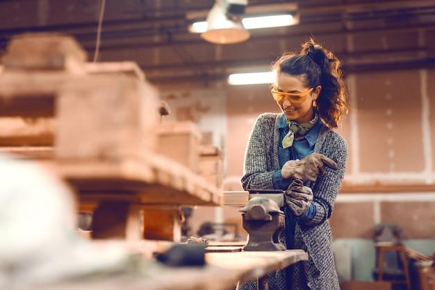 Garota trabalhando na braçadeira com óculos de proteção.