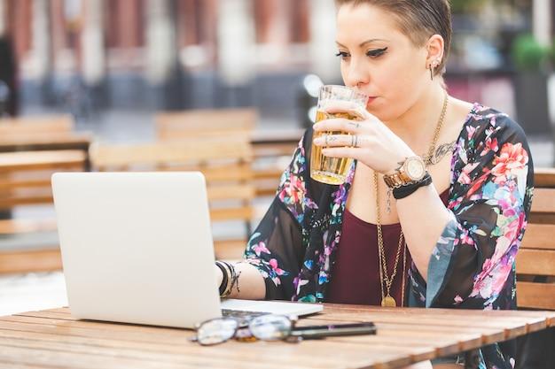 Garota trabalhando no computador dela e bebendo cerveja