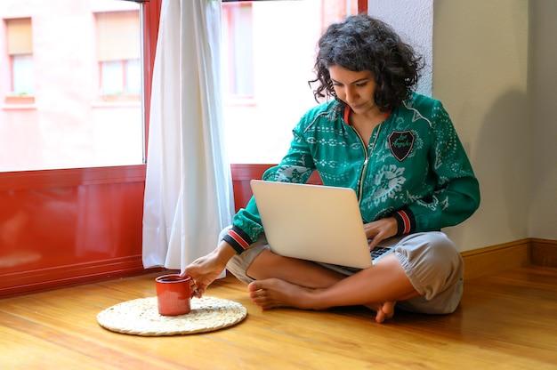 Garota trabalhando no laptop em casa ou estudante estudando em casa ou freelancer.