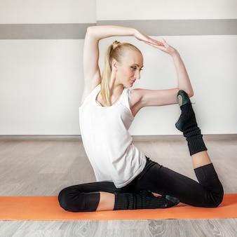 Garota treina no ginásio. quadrado. o conceito de esporte, dança e saúde